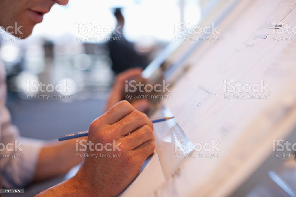 Businessman drawing on drafting table in office stock photo