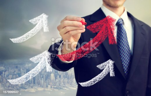 Businessman drawing rising arrows in the city