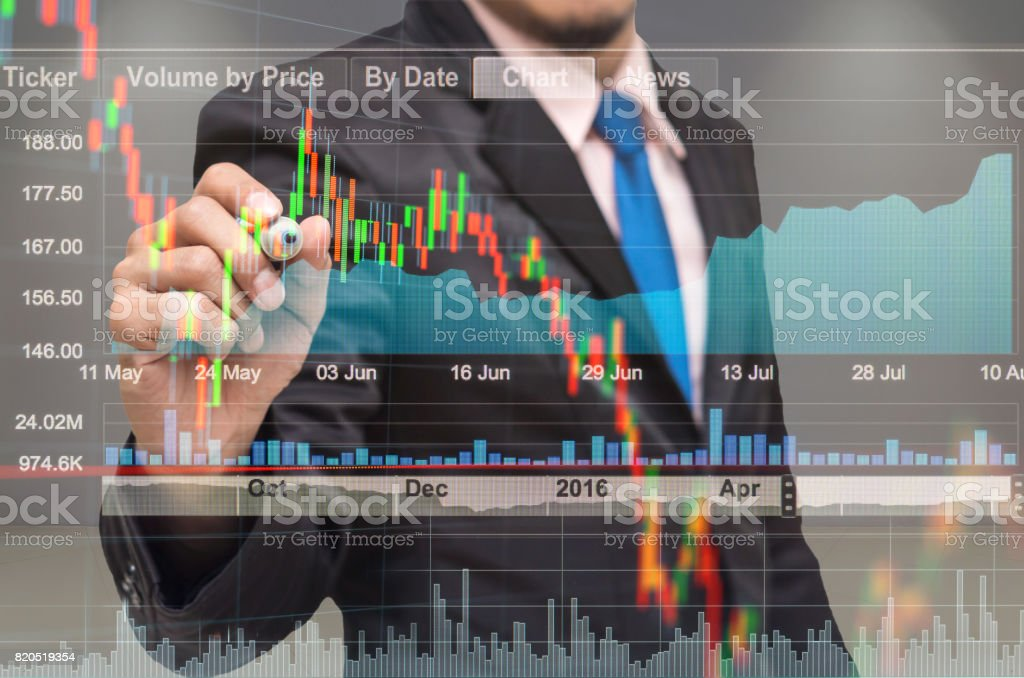businessman drawing the stock graph with stock market exchange over the trading room , business marketing concept stock photo