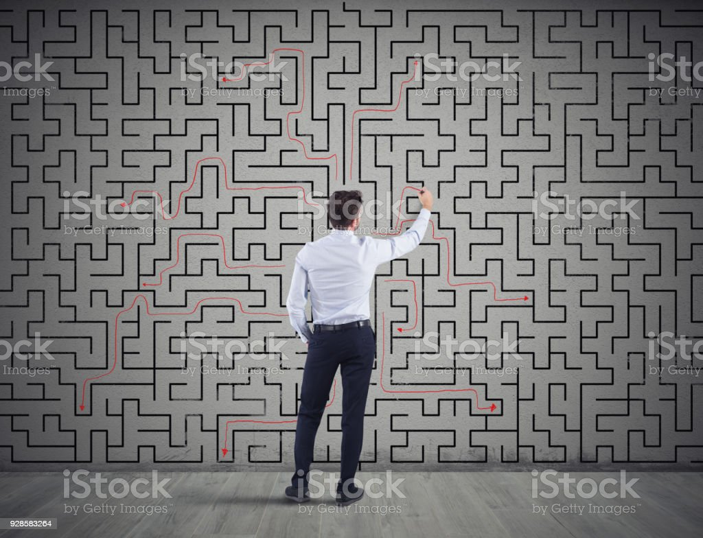 Businessman draws the solution of a labyrinth. Concept of problem solving foto stock royalty-free