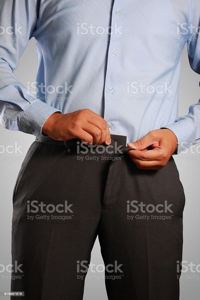 Businessman Dressing, Pulling His Pants Placket stock photo