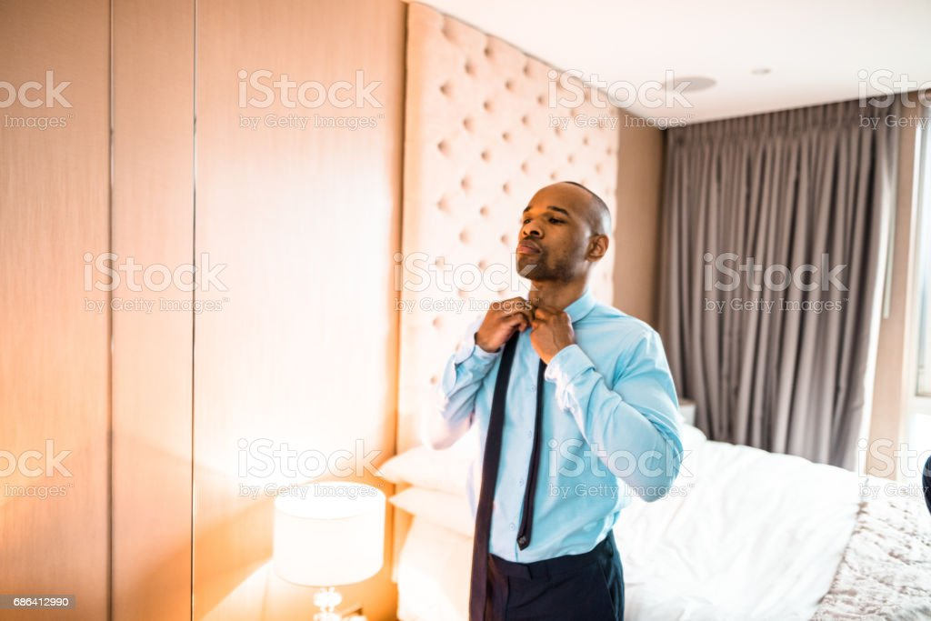 businessman dressing up sitting on the bed stock photo