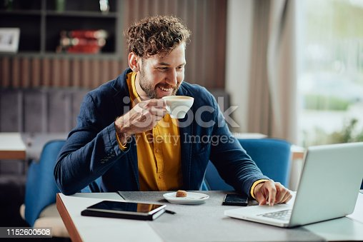 istock Businessman drinking coffee and looking at laptop while sitting in cafe. 1152600508
