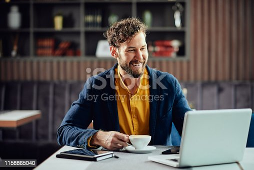 Bearded smiling Caucasian freelancer sitting in cafe, drinking fresh coffee and using lapotp.