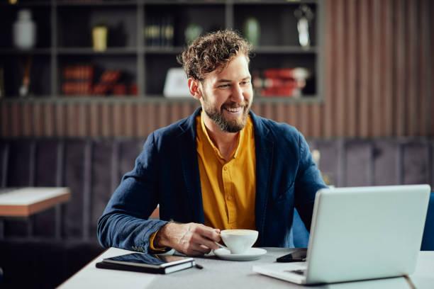 Geschäftsmann trinkt Kaffee und schaut auf Laptop, während im Café sitzen. – Foto