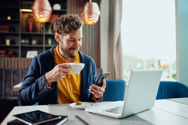 Geschäftsmann trinkt Kaffee und benutzt Smartphone im Café. – Foto