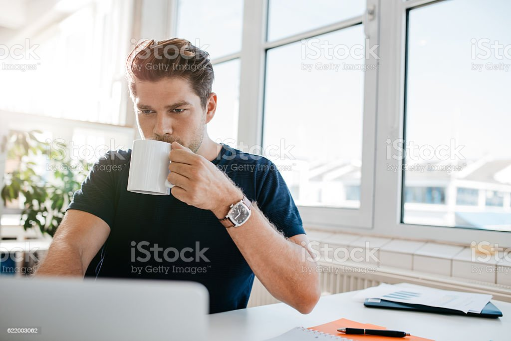 Businessman drinking coffee and working on laptop at office - Photo