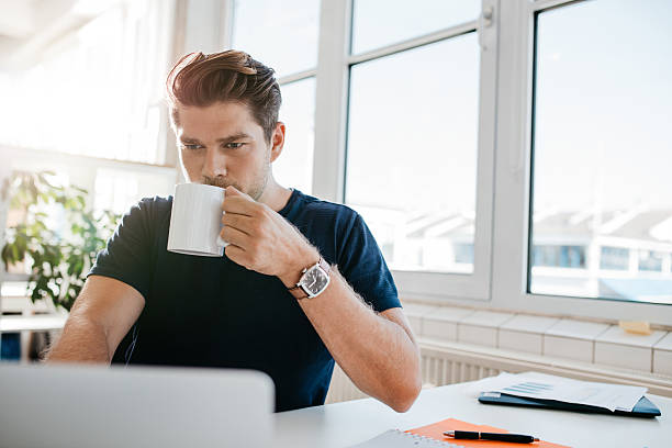 Businessman drinking coffee and working on laptop at office stock photo