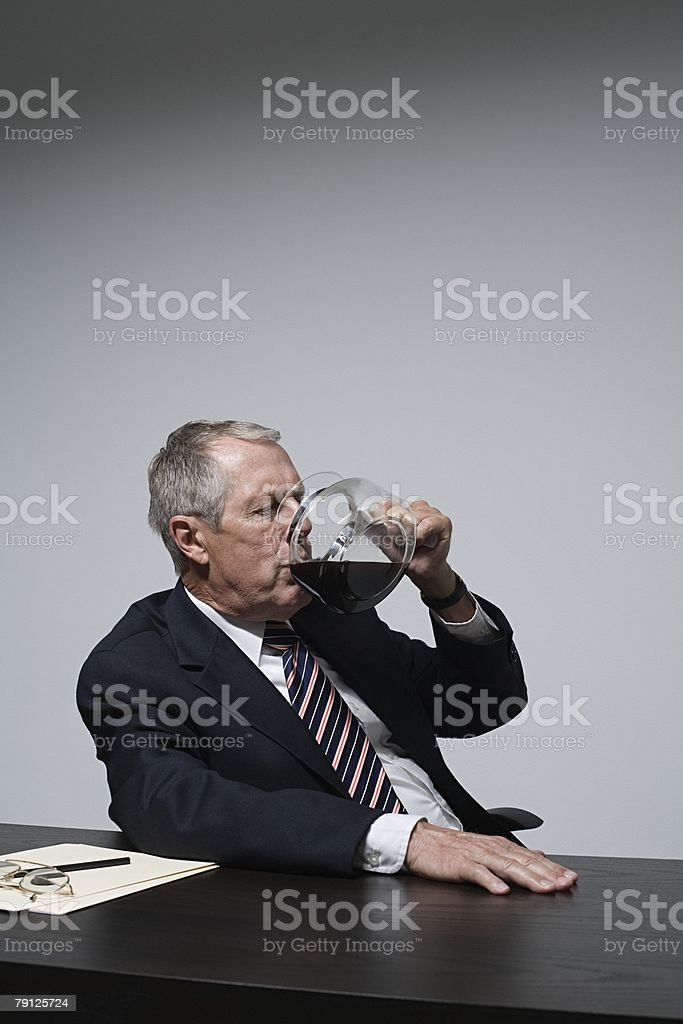 A businessman drinking coffee from a coffee pot royalty-free 스톡 사진