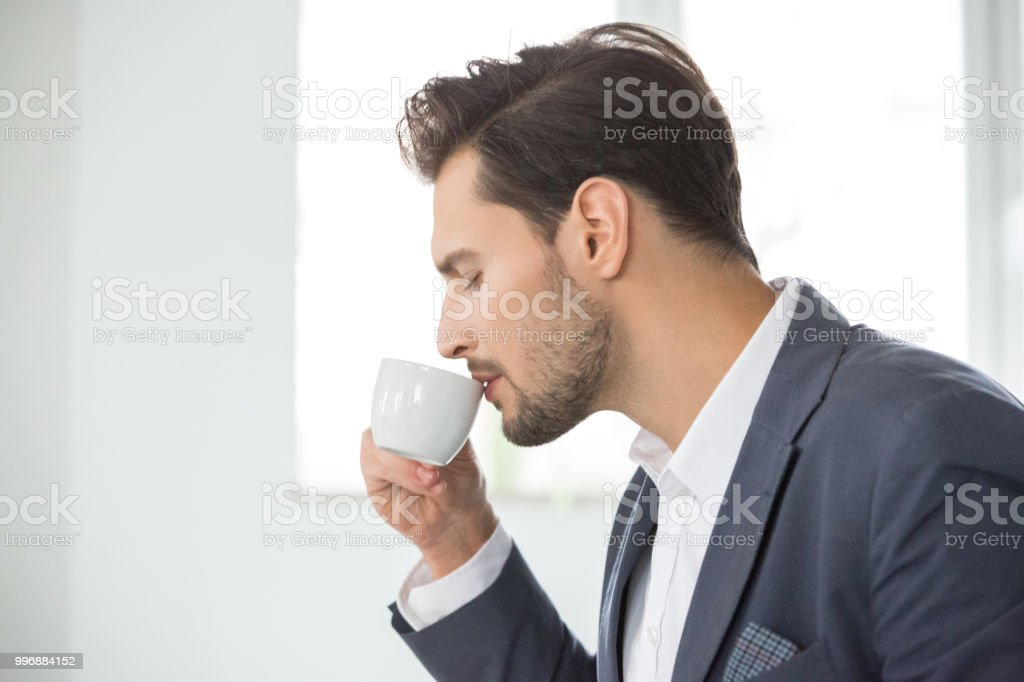Businessman drinking coffee in office Side view of young man drinking coffee in office. Business professional having coffee break at his work place. 25-29 Years Stock Photo