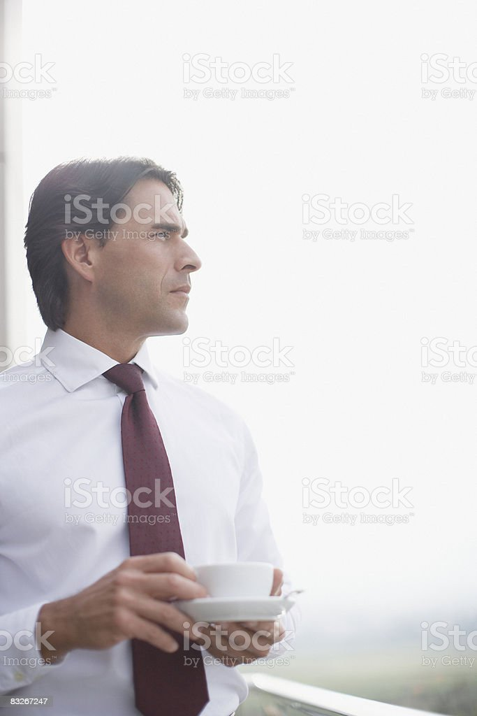 Businessman drinking coffee on balcony royalty-free stock photo