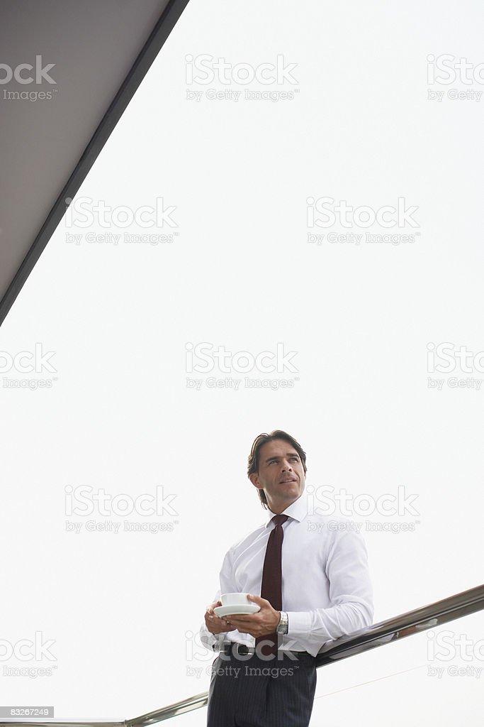 Uomo d'affari di bere il caffè in balcone foto stock royalty-free