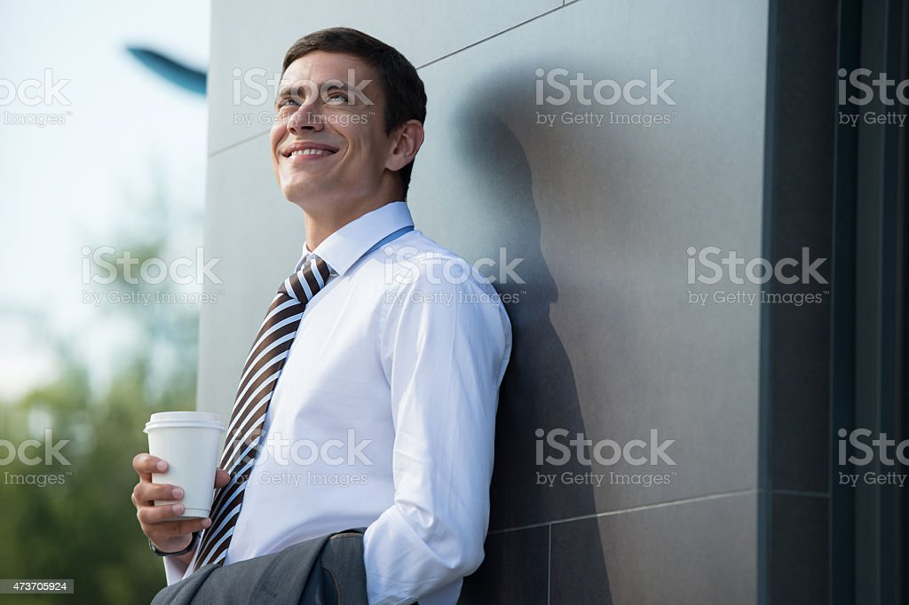 Businessman drinking coffee outdoors stock photo
