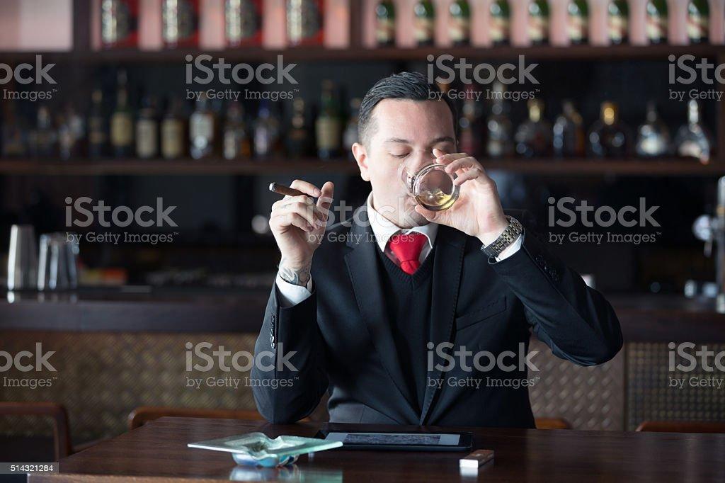 Businessman drinking scoth and  smoking cigar stock photo