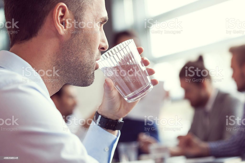 Businessman drinking water at the meeting Close up of businessman drinking water at the meeting.  In the background blured business team discussing in a board room in an office. 2015 Stock Photo