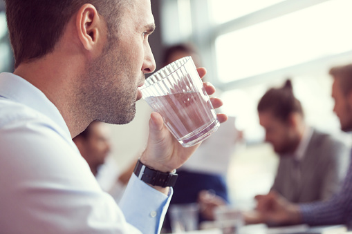 Businessman Drinking Water At The Meeting Stock Photo - Download Image Now