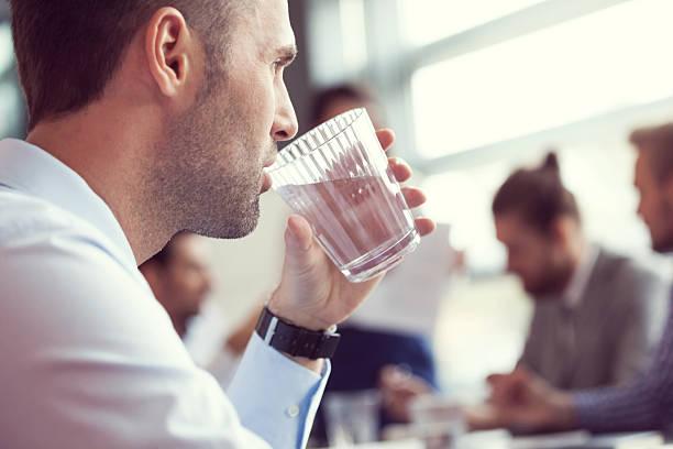 geschäftsmann trinken wasser im meetingraum - leitungswasser trinken stock-fotos und bilder