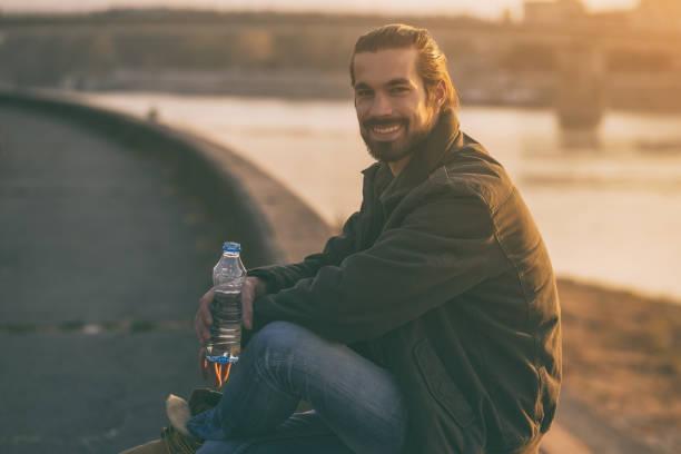 Geschäftsmann Trinkwasser bei einer Rast am Fluss – Foto