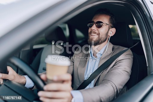 Handsome Elegant Bearded Mid Adult Businessman in Full Suit Drinking Coffee to go While Driving a Car. Businessman Manager Driving Car While Drinking a Cup of Coffee
