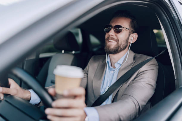 Businessman Driving Car While Drinking Coffee stock photo
