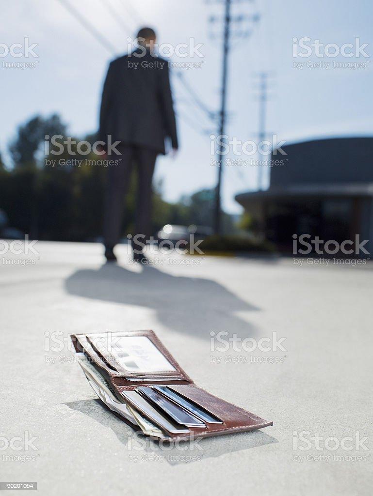 Businessman dropping wallet on sidewalk royalty-free stock photo