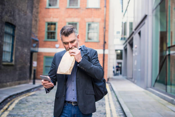 Businessman eating a sandwich and using smart phone stock photo
