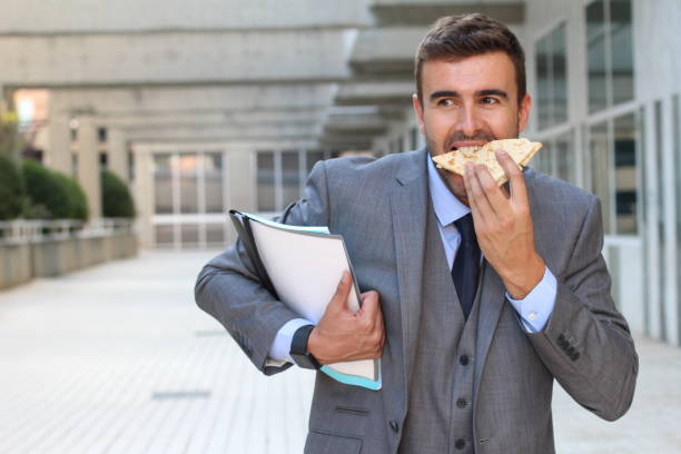 Businessman eating a sandwich on the go stock photo