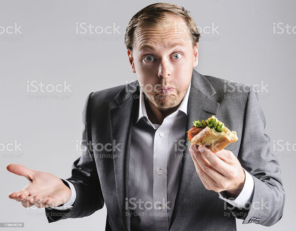 A businessman eating a sandwich stock photo