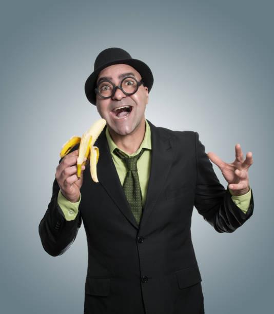 hombre de negocios comiendo plátano - studioimagen73 fotografías e imágenes de stock