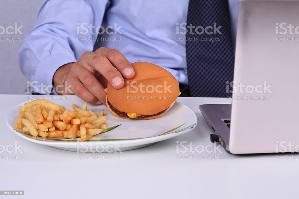 Businessman eating hamburger in an office. royalty-free stock photo