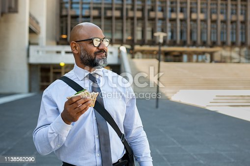 Mature african businessman in formal clothing eating brown bread sandwich outdoor. Senior entrepreneur wearing spectacles standing outside office building, looking away while enjoying vegetable sandwich. Business man having lunch on the move.