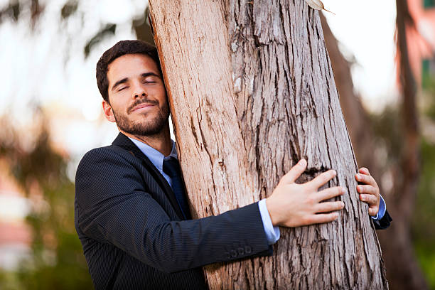 Businessman embrace a tree trunk stock photo