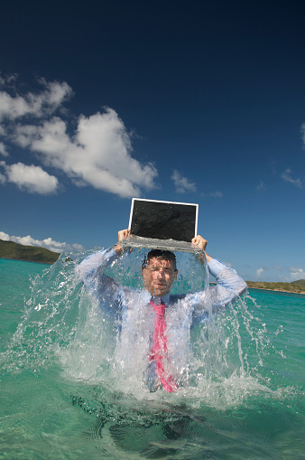 1044507110 istock photo Businessman Emerges from Water w Laptop 173864207