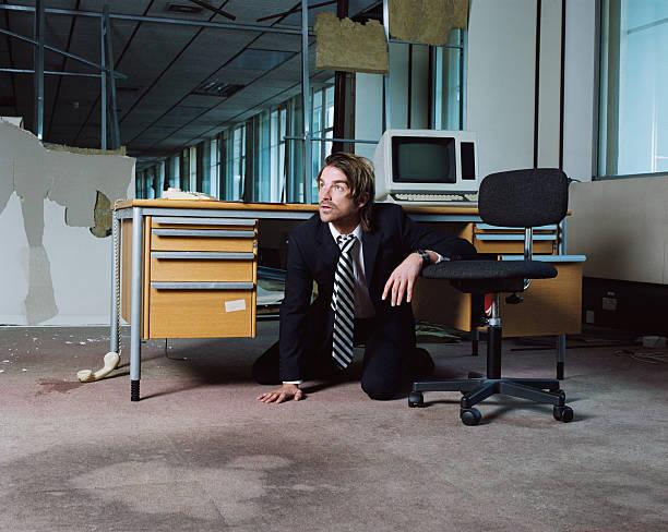 Businessman emerging from under desk stock photo
