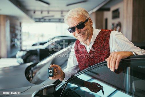Senior man holding the car keys of his new car