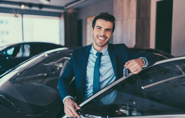Businessman enjoying new car Man holding the car keys of his new car car salesperson stock pictures, royalty-free photos & images