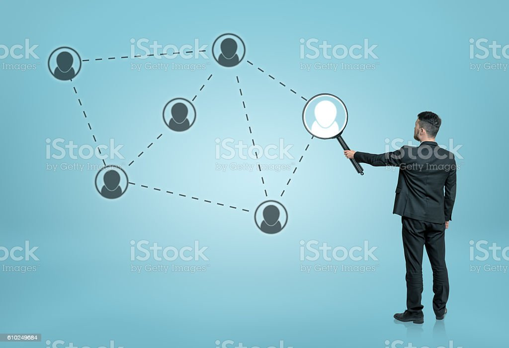 Businessman enlarging one of the social network icons connected by stock photo