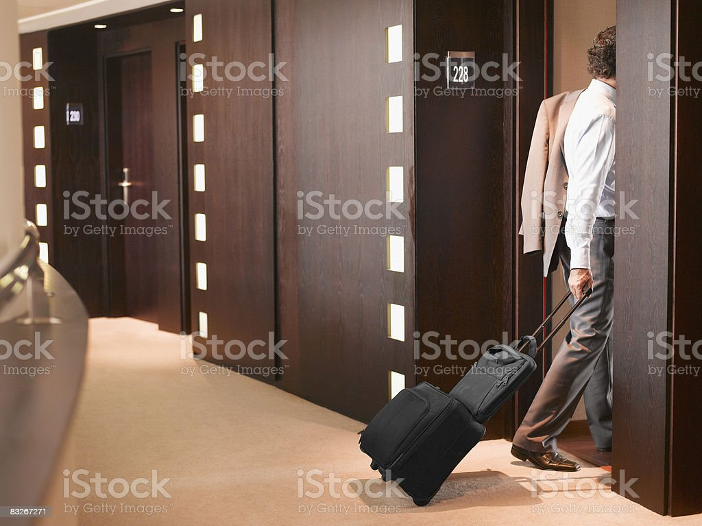 Businessman entering hotel room with suitcase stock photo