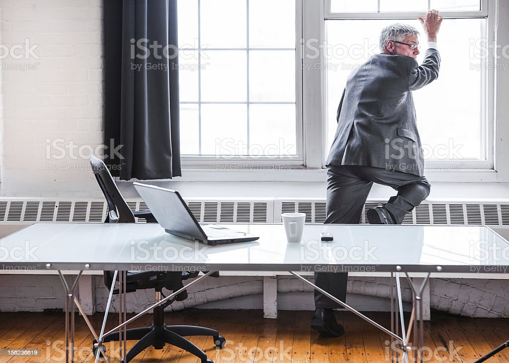 Businessman escaping or jumping out of an office window stock photo