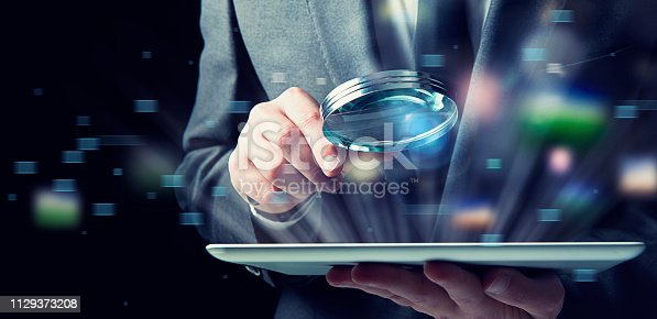 Businessman examines an infected tablet with a magnifying glass. Concept of internet security
