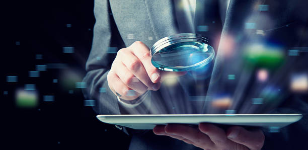 Businessman examines a tablet with a magnifying glass. Concept of internet security - foto stock