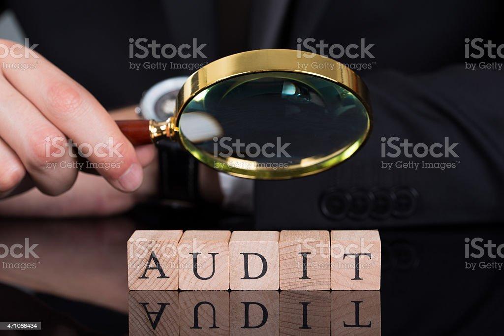 Empresario examinar bloques de auditoría a través de lupa - foto de stock