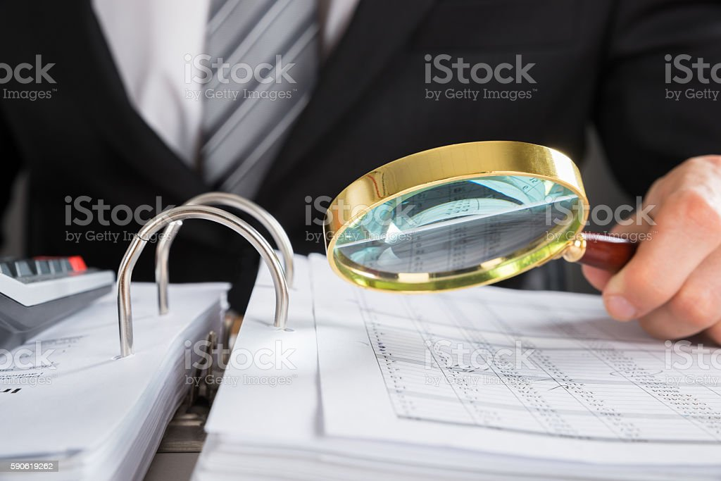Businessman Examining Invoice With Magnifying Glass stock photo