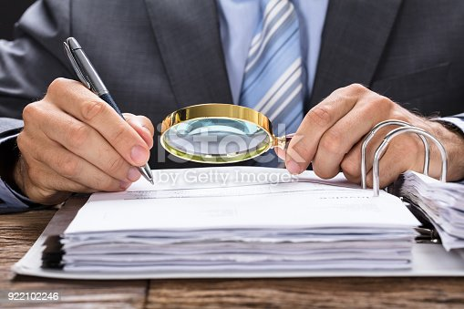 istock Businessman Examining Invoice With Magnifying Glass 922102246