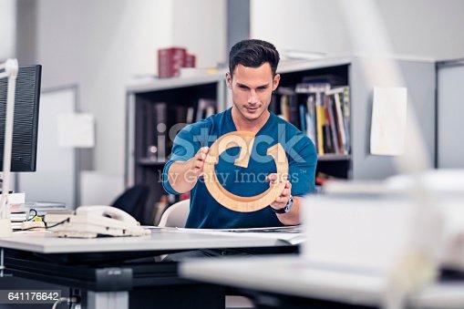 istock Businessman examining model at desk in office 641176642