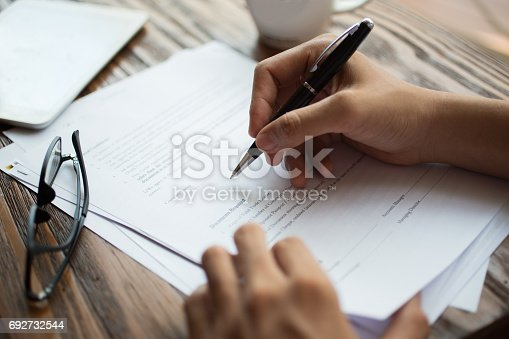 Unrecognizable businessman examining papers at table. Manager with ballpoint pen filling business papers. Close-up of male hands working at desk. Analyzing documents concept
