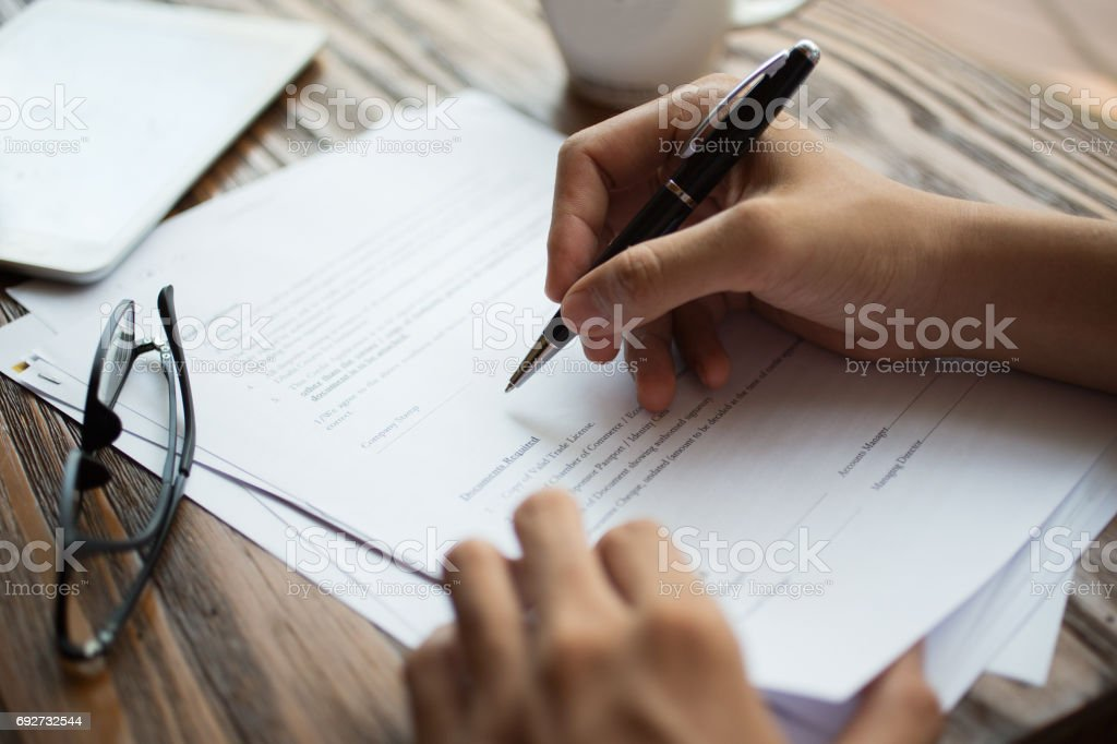 Businessman examining papers at table stock photo