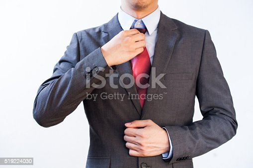 516141885istockphoto Businessman Executive adjusting red tie isolated on white background 519224030