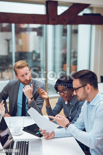 Young businessman is explaining business plan to coworkers during business meeting in the office.