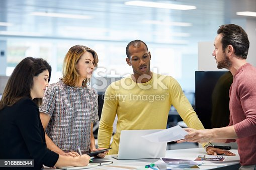 1150572092istockphoto Businessman explaining colleagues at office 916885344